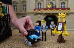 Lego models of Prince William, the Duke of Cambridge & Catherine, The Duchess of Cambridge along with a pram containing a model of their newborn baby boy George Alexander Louis are postitioned outside a 36000 Lego-brick  model of Buckingham Palace at Legoland in Windsor on July 25, 2013.  AFP PHOTO / ANDREW COWIE/AFP/Getty Images