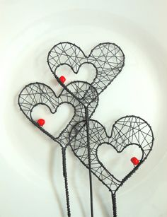 Wire hearts with a red bead.