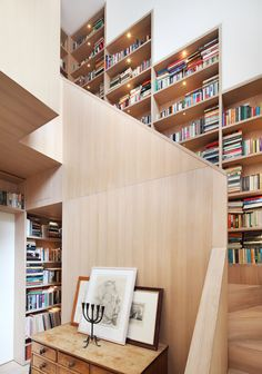 12 Inspiring Examples Of Staircases With Bookshelves | This staircase/library combo is in the center of this London home, and small lights ensure that everything is on display.