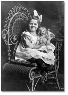 Little girl wearing a pinafore has big smile, a big bow in her hair and andher doll in the crook of her arm. Circa 1890's - 1910's.