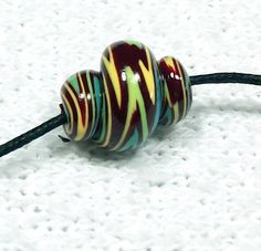 This unique set of spiral handmade polymer clay beads are crimson, turquoise and sunshine yellow. Twisted and swirled these interesting beads are one of a kind. You will receive the exact 8 beads shown. The hole is large enough for a 1mm cord if you want to use them for a macrame project. The size is shown next to a ruler in pic #3. They have a gloss finish.