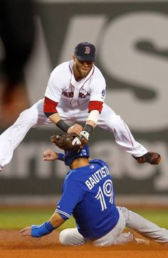 BOSTON, MA - JUNE 27: Dustin Pedroia #15 of the Boston Red Sox turns a double play as Jose Bautista #19 of the Toronto Blue Jays slides late in to second base in the 4th inning at Fenway Park on June 27, 2013 in Boston, Massachusetts. (Photo by Jim Rogash/Getty Images)