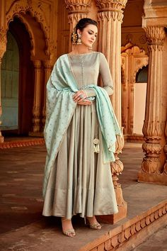 Spell sophistication with this grey designer anarkali falling plain all over with the neckline done in zari and Kundan work while the front bears sea green loops for pattern. This suit is accompanied with matching leggings and a contrasting sea green Dupatta displaying sequin and zari motifs all over the expanse for decor!