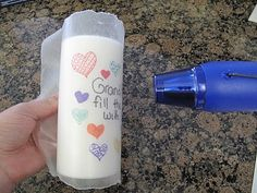 Draw on wax paper with permanent markers, wrap around candle and heat until image is transferred. Great gift idea!