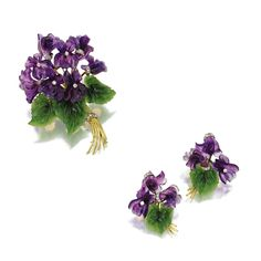 CARVED AMETHYST, NEPHRITE AND DIAMOND 'VIOLET' BROOCH AND MATCHING EARCLIPS Designed as bunches of violets, the petals formed of carved amethysts, the leaves of carved nephrite, accented further with small round diamonds weighing a total of approximately 1.10 carats, mounted in gold.