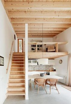 Open plan living space with exposed wood structure, wooden staircase and mezzanine floor. Love the tiling in the kitchen