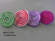 originales anillos con base ajustable plateada y aplicación en forma de espiral sobre fieltro con cola de ratón de brillo en tonos rojos, platas, morados, verdes ..., entrelazándo dos colores para mayor vistosidad