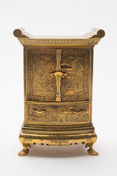 A Japanese Komai iron miniature cabinet: engraved and gilded overall with river and landscape scenes with pagodas, boats and irises within diaper and floral borders, the two doors enclosing an arrangement of drawers and shelves around an arched bridge, on shaped bracket feet, signed on inner back panel, Meiji, 22cm high.