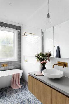 a modern space with mosaic tiles, grey subway tiles, a wood and concrete vanity and metallic fixtures
