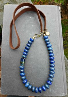 Blue Lapis Lazuli stone, bronze metal, lamp work glass bead and leather. Total necklace measures 24-25 inches long. As with all of my jewelry this is lead and nickel free. All of my jewelry is made by