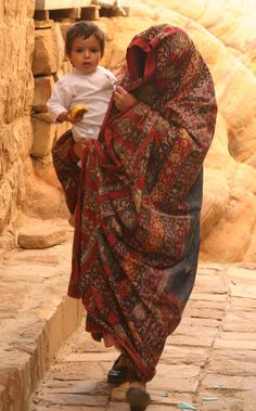 https://flic.kr/p/zuRE9 | yemen | Veiled Yemeni woman with child in the streets of Thilla. Thilla is a rare example of an almost perfectly preserved highland town of stone tower houses.