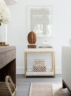 """The bar cart is covered in capiz—part of the mission to add rich texture everywhere. """"There's no real color here,"""" Alex says, """"but the capiz makes the whole spot dynamic."""" And bytucking the shell and books below, Erin and Gabe can easily turnthe spot into a setup for drinks when theyentertain."""