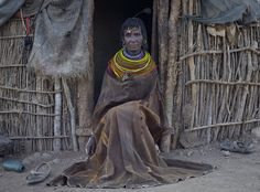 Africa |  Turkana tribal elder in front of her home, wearing traditional goatskin cloak, Nakuprat village, Nakuprat-Gotu Community Conservancy, Kenya | © Chris Jordan