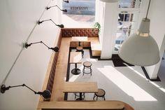 Restoration Hardware Swing Arm Wall Lights, Hudson Valley Vintage Pendants, large Banquette Seating, Penny tile with black border. Coffee Shop Interior design.
