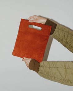 LPB Clutch in Rust Suede. A soft leather clutch with cut-out handles, styled after a simple flat plastic bag. Carry by top handles, or fold and tuck under arm.