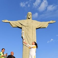 Former Brazilian volleyball player Maria Barroso holds the Olympic torch aloft in Rio