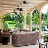 With no inch left unfinished, this lavish living space is appointed with dramatic arched columns, comfortable seating, a dining room, natural stone flooring, lush vegetation, and a glistening pool. | HGTV FrontDoor