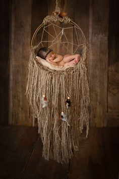 This beautiful, rustic dream catcher is made of a wood base and a hand made wood bottom. It's rustic and unique! It's made with yards and yards of jute, a few natural colored feathers flowing softly within the wood beads. For added character there is one bead woven into the netting behind baby and three silver toned feathers. All will be similar, no two will be identical! So...each will be a one of a kind! Should you have a special request in regards to feather or bead colors, ...