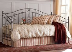Reminiscent of turn-of-the-century garden gates, our Irongate daybed flaunts exquisite scrollwork. This piece has a pewter finish and topped with round finials. Strongly welded iron. Link spring required.