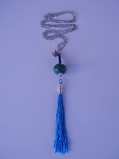 Long silver nacklace made of a green #stone bead and blue thread #tassels. Very uniq and brave combination. www.ayaglass.hu