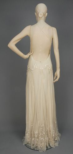 UNLABELED ALEXANDER McQUEEN EMBROIDERED CHIFFON EVENING GOWN.  Bias cut backless cream silk with crossed spaghetti straps, having dropped waist with inverted scallops and satin stitch floral embroidery, matching hem decoration and layered silk underdress.
