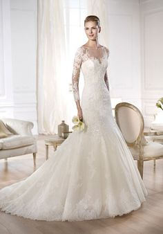 Pronovias Glamour Collection -- Ocymar  Tulle petit pois dress covered by a layer of natural white tulle with Chantilly and guipure lace appliqués and mother-of-pearl precious stones. Bateau neckline with long sleeves covered in appliqué and sheer layer over a heart-shape neckline.