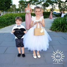 Awww isn't this cute! Jessica's flowergirl and pageboy carrying the here comes the bride sign!  Bridesmaids: @godessbynature Signature Ballgowns in Dust Me Pink colour