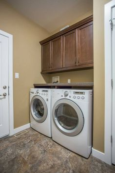 Side By Side Washer And Dryer, With Counter And Cabinets Above.