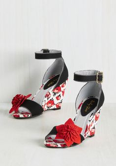 Raise the stakes on ravishing style with these sassy fabric wedges! Though their solid black bands may seem simple, a second glance reveals finely dotted trim, flower-touched toes, and ivory, red, and pink blossoms atop which your well-crafted look stands. Unforgettably fab!