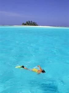 Woman Snorkelling at Sea Surface,Cocos Keeling Island in Background, Indian Ocean, Australia