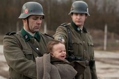 CAVEAT: This is a publicity still from the dramatic film AUSCHWITZ (2011), and not a genuine wartime image. Its composition and resolution are untypical of true period photographs. It is highly unlikely that the SS-men depicted would permit clear pictures of a war crime. Moreover, consider the unlikelihood of the photographer standing in the line of fire of the purported executioner's pistol. Finally, the SS collar insignia look like reproductions.
