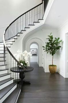 Chic, classic foyer features a curved staircase wall filled with a black round table and orchids. Chic, classic foyer features a curved staircase wall filled with a black round table and orchids. Foyer Staircase, Curved Staircase, Staircase Design, Staircase Ideas, Foyer Design, White Staircase, Entrance Foyer, Grand Entrance, Design Bedroom