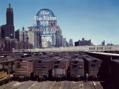 A sign advertising Pabst Blue Ribbon beer lights up the surrounding Illinois Central Railroad freight cars parked in Chicago's South Water Street freight terminal.