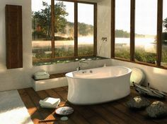 bathtub with large window view of steamy lake