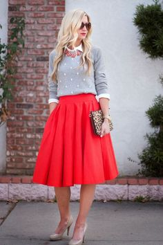 nude heels, a red midi skirt, a white shirt, an embellished grey sweater and a statement necklace for a holiday look
