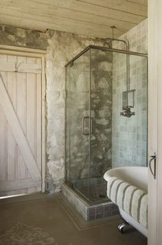 Rustic Bath  This modern glass shower disappears into the stone wall. The whitewashed, wide-plank Z door adds softness to this weathered room. Rough wood above is the perfect ceiling choice. Carry the look all the way through every detail with antique hooks and door latches. Keep it honest with exposed plumbing and electrical conduits whenever possible.