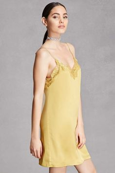 This satin woven slip dress features a delicate eyelash lace trim at its V-neckline, adjustable straps, a scoop back, and a slightly oversized silhouette. This is an independent brand and not a Forever 21 branded item.