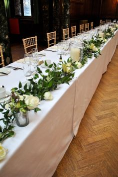 Foliage garland with flowers and candles along the top table. Something along these lines, with softer foliage and some hints of soft pink too.