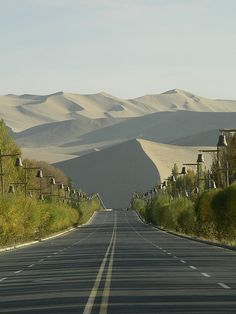 Mingsha Shan, located in China's Taklamakan Desert, is a dune field known for the phenomenon of singing sand. The road banked with bells on poles fascinates me - what are they? Beautiful Roads, Beautiful World, Beautiful Places, Places To Travel, Places To See, Ansel Adams, China Travel, Pathways, Land Scape