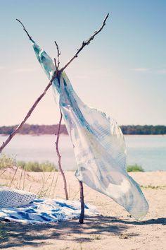 Isot rantahuivit toimivat yhtä hyvin alustana kuin pyyhkeenä. Muutaman ison oksan avulla huivista saa pystytettyä aurinkokatoksen tai leikkiteltan.