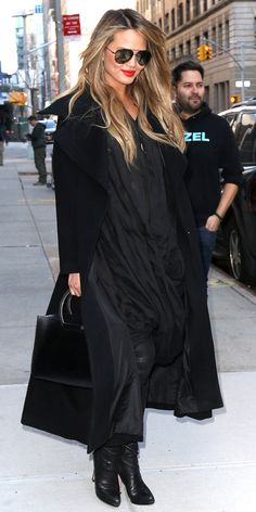 Teigen let her tresses loose and added a bold red lip and a cozy long coat. The model looked like the quintessential New Yorker with her all-black ensemble and roomy tote.