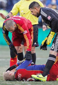 Real Salt Lake defender Chris Wingert (17) and goalkeeper Nick Rimando (18) check on defender Nat Borchers (6) after he was hit in the face with the ball. The frigid temperature in KC made matters worse.