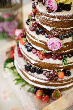 naked wedding cake with each layer covered in berries and dusted with icing sugar