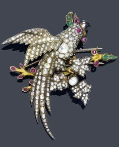 AN ANTIQUE DIAMOND, RUBY AND EMERALD CLIP BROOCH, CIRCA 1900. Designed as a cockatoo set with rose-cut diamonds and 12 small rubies and six emeralds, with a later branch and brooch mount, mounted in silver topped pink and yellow gold. 8.5 x 8 cm. #antique #ClipBrooch