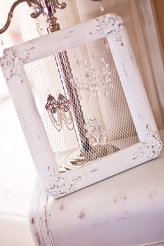Old frame with chicken wire to hold earrings. Would be cool mounted like a real picture...just spaced out from the wall.