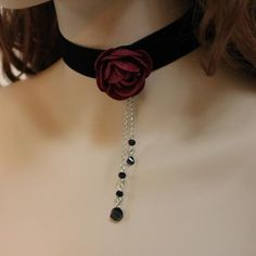 Romantic Victorian! Luxurious black velvet choker with a pretty red felt rose. Dangling black faceted beads add a bit of sparkle to this unique choker necklace.