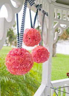 Coral flower balls / pomanders hang from the arbor with Navy Blue and White Chevron Ribbon by Andrea Layne Floral Design (www.andrealaynefloraldesign.com)