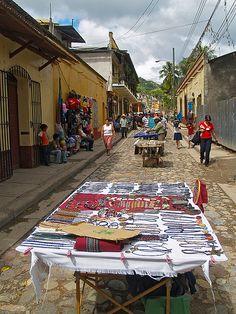 La calle de los artesanos en Copan Ruinas. Cada fin de semana, esta vía se cierra al tránsito vehicular convirtiéndose en una peatonal donde los artesanos locales e internacionales exponen sus magníficas obras, las cuales estána la venta a precios muy razonables. Es una de las cosas de las que pueden disfrutar los visitantes en este pacífico y encantador pueblecito del Oeste de Honduras, además de las magníficas Ruinas de Copán.