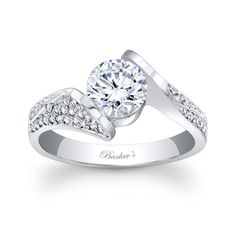 Stunning and unique this diamond engagement ring exudes confidence for the woman who wears it.  Featuring a low profile cathedral shank that rises to capture the channel set round diamond center securely  in it's grasp, while pave set diamonds cascade down the shoulders.