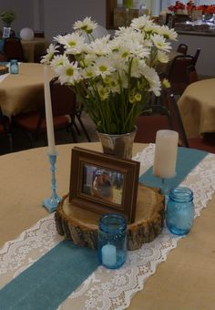 Table décor at wedding reception with burlap table cloths, lace runners with turquoise burlap ribbon overlapped, wood charger, turquoise mason jars with candles, and painted candle sticks